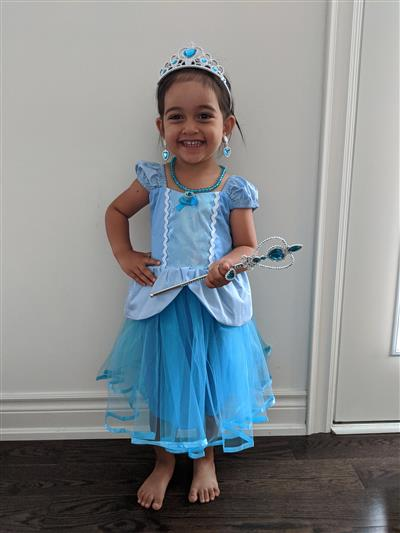 Child in Halloween costume: Princess or Queen (blue dress and accessories) with crown, necklace, and wand.