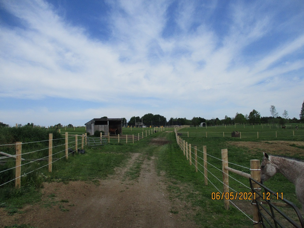 Country property driveway with a stable