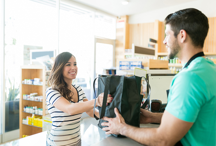 Woman receiving purchased products in reusable bag