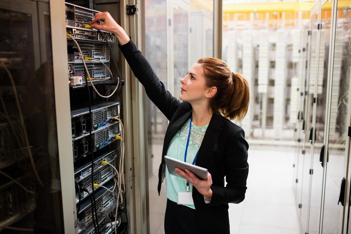 A woman holding a tablet and examining a business server.