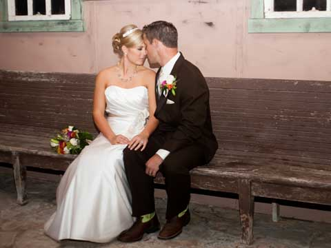 bride and groom on rustic bench