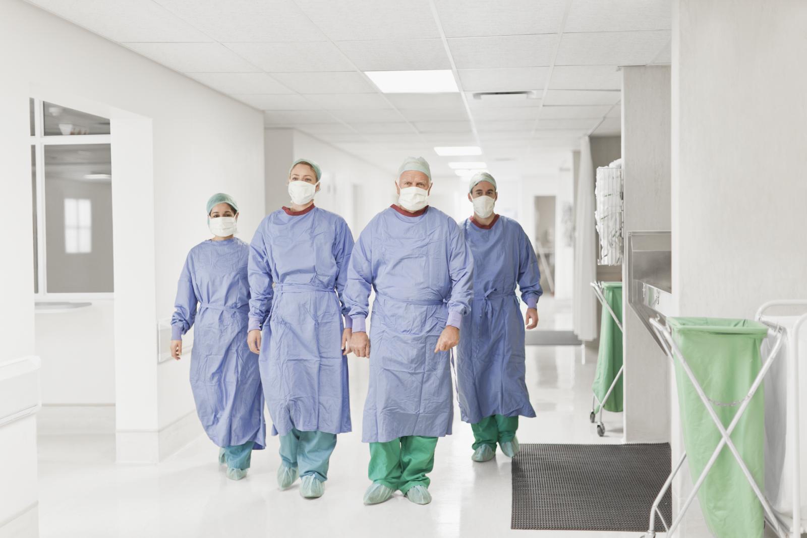 team of surgeons walking down hospital hallway