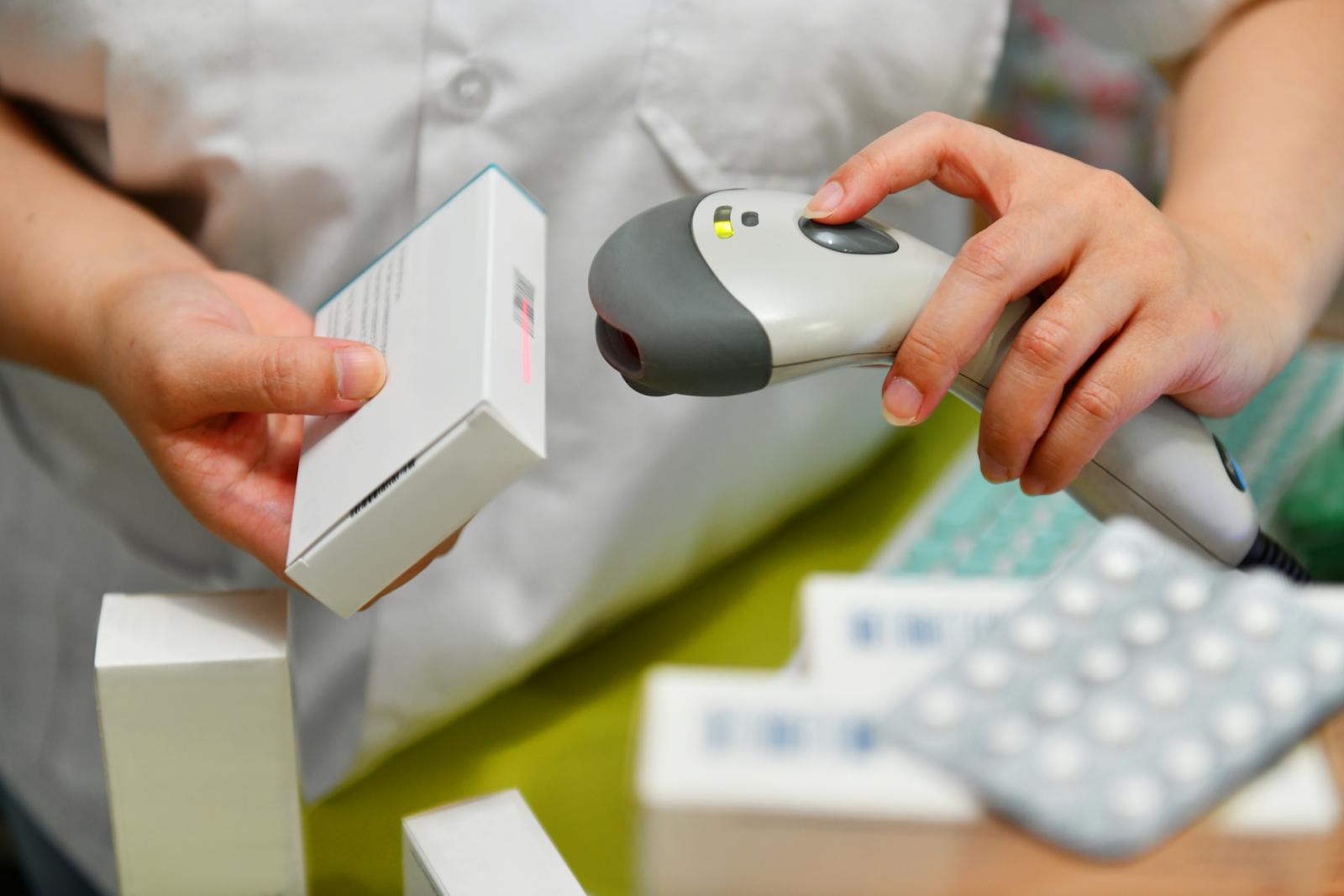 Pharmacist scanning barcode of medicine drug