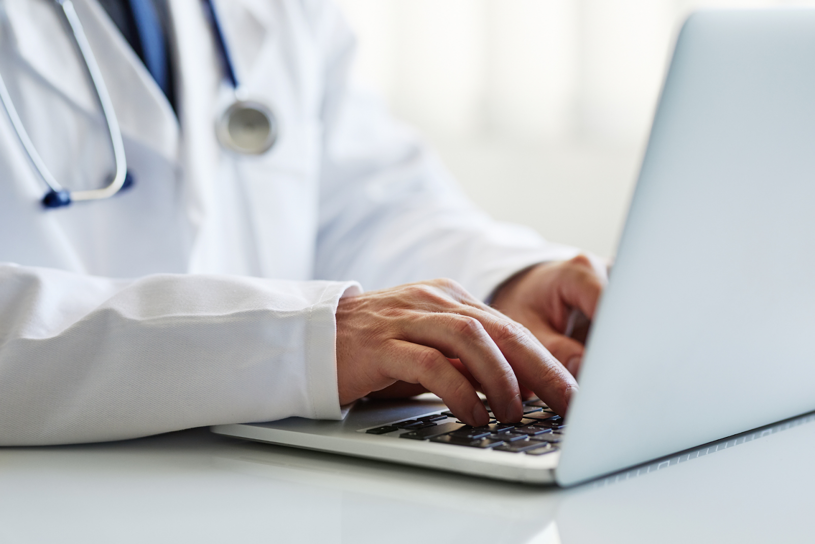 physician entering information into laptop