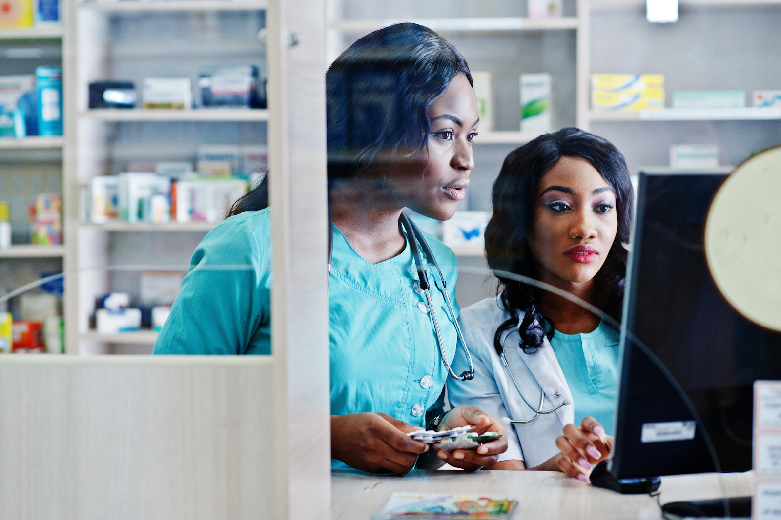two pharmacists looking at a computer screen