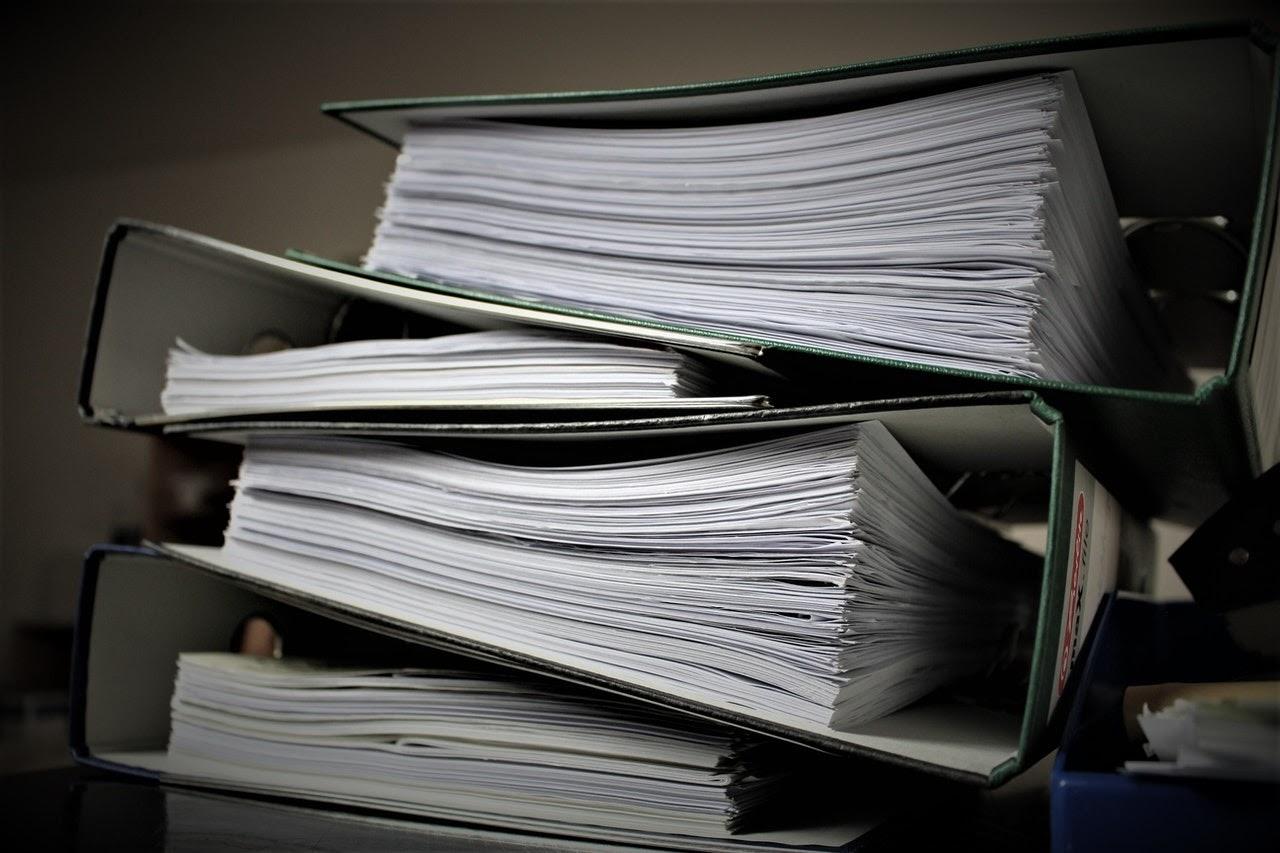 large stack of files paper binders gray dark stack