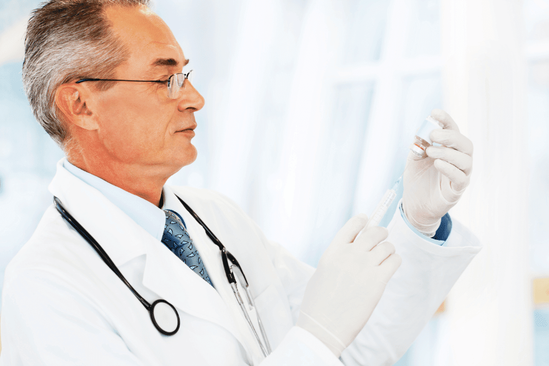 doctor with stethoscope filling syringe white background gray hair glasses