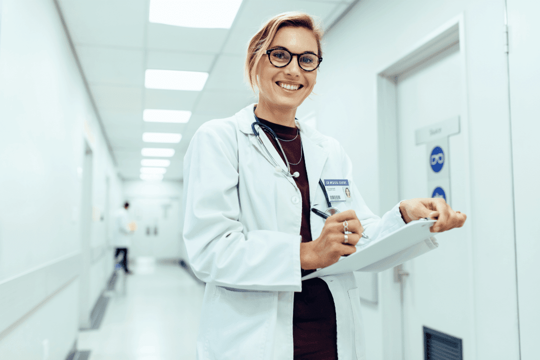 healthcare worker in hallway holding clipboard glasses smiling