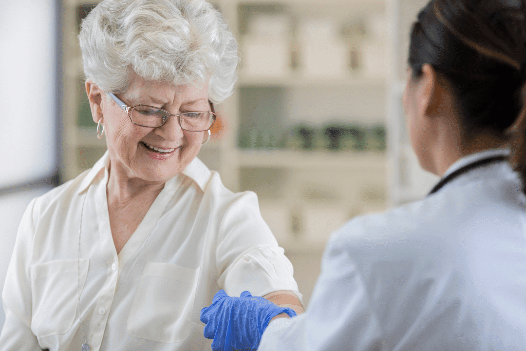 older woman receiving vaccine from young healthcare provider vaccination clinic smiling