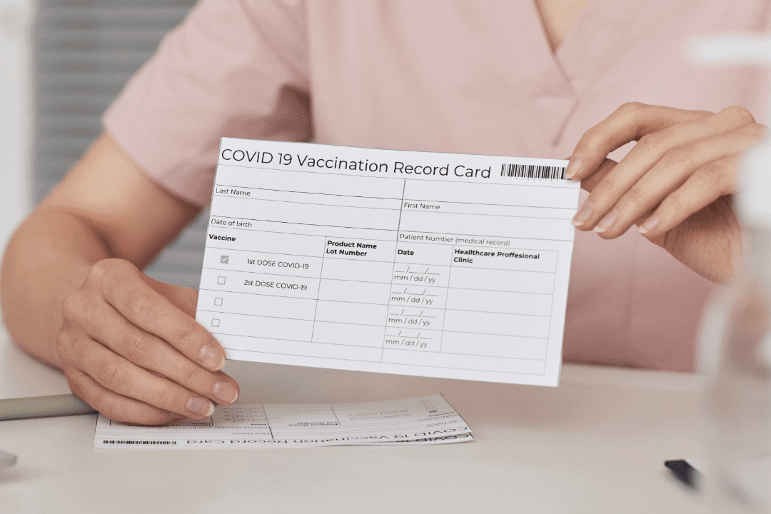 COVID-19 vaccination card held up by woman healthcare worker fingernails vaccination clinic