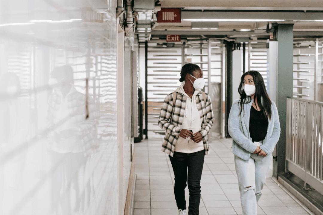two young women walking in subway metro area trendy clothes white tiles conversation white masks