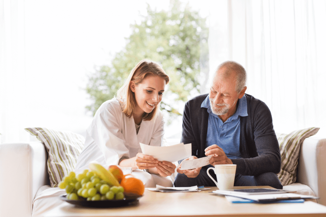 young woman showing older man medical records in retirement home smiling fruits  coffee folders tree in background