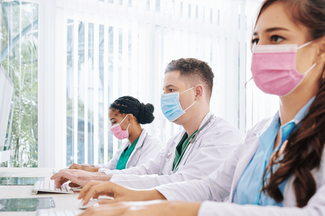 three healthcare workers wearing surgical masks data entry bright background typing on computers