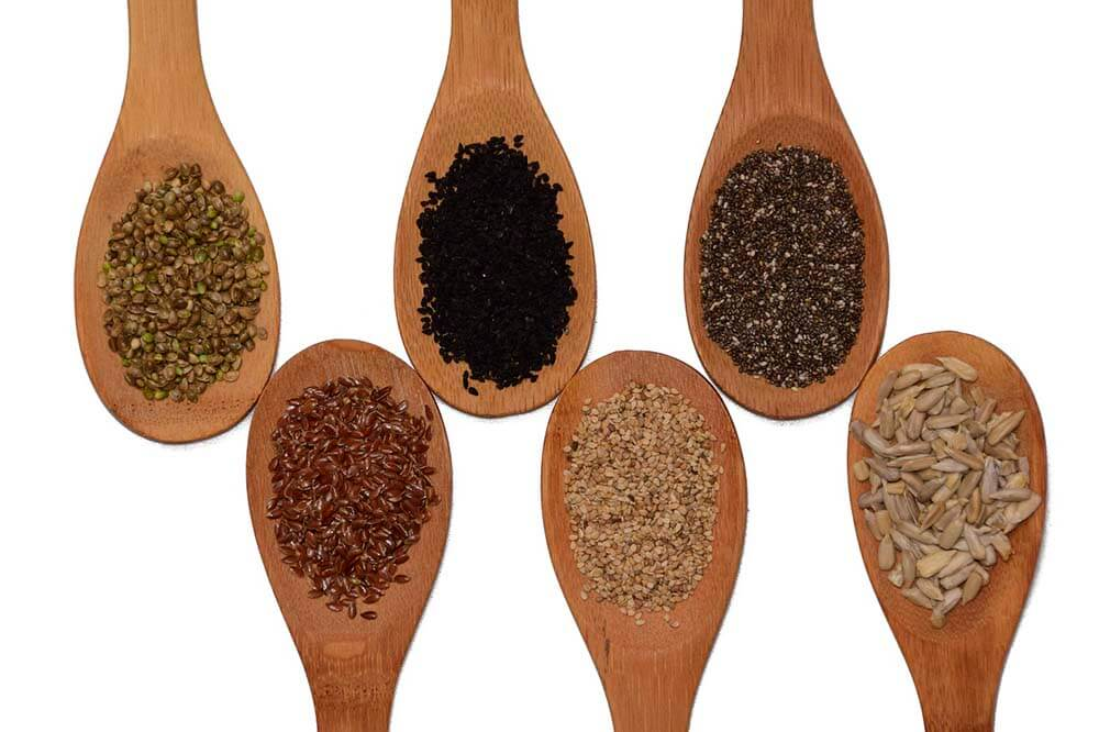 different seeds on wooden spoons