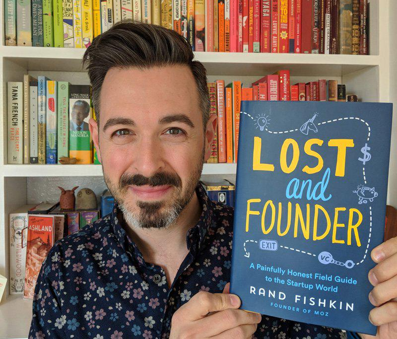 This is a picture of a man holding a book. He is the author of this book. This is a photo of Rand Fishkin, former CEO of Moz, a SaaS SEO product.