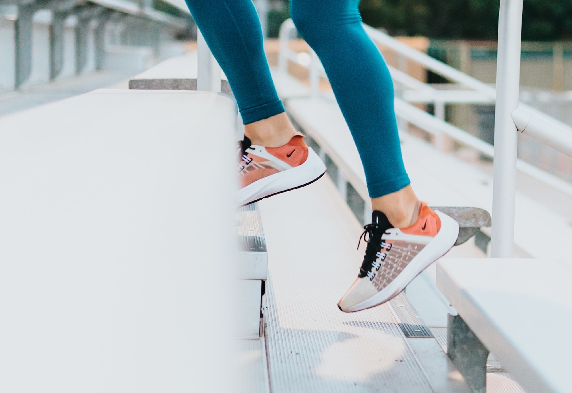 This picture shows a woman running up bleacher stairs wearing nike sneakers and teal leggings. This is a photo abaout fitness and performance footwear