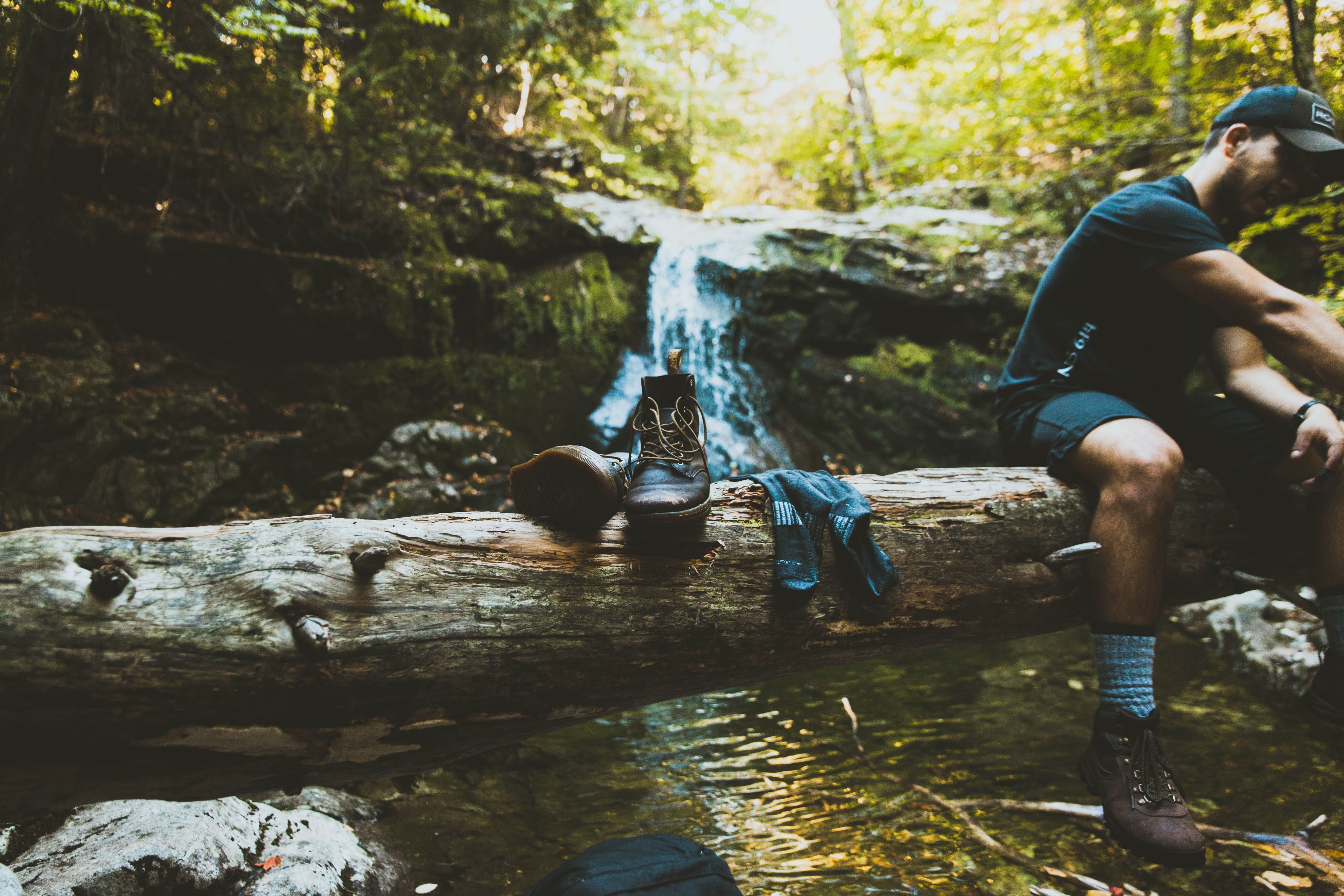 This is a picture of a man on hike, resting by a small waterfall. He is wearing boots with socks and sitting on a log.
