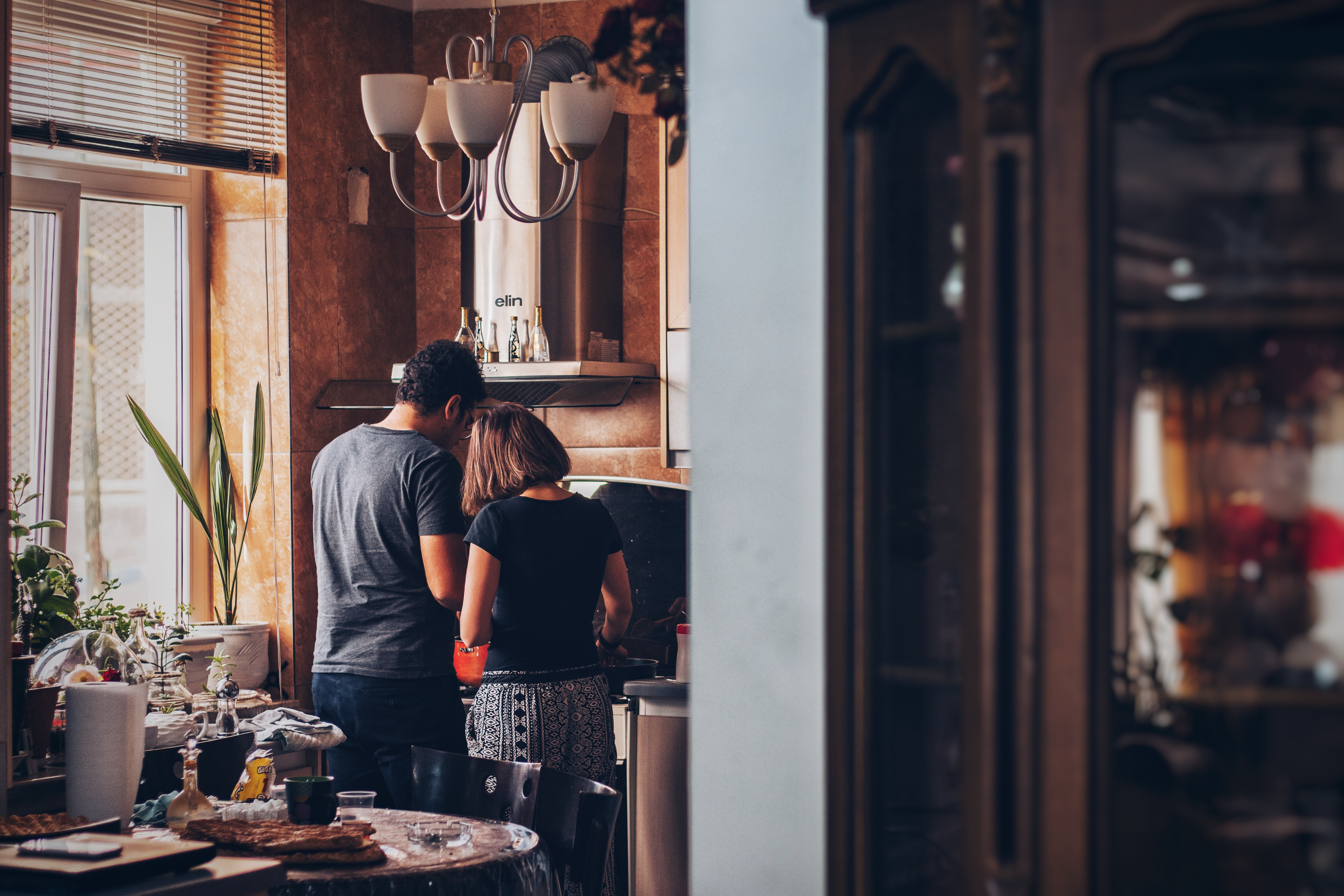 This is a picture of two people cooking in their kitchen. This is a photo of a couple cooking dinner by a window with stainless steel appliances.