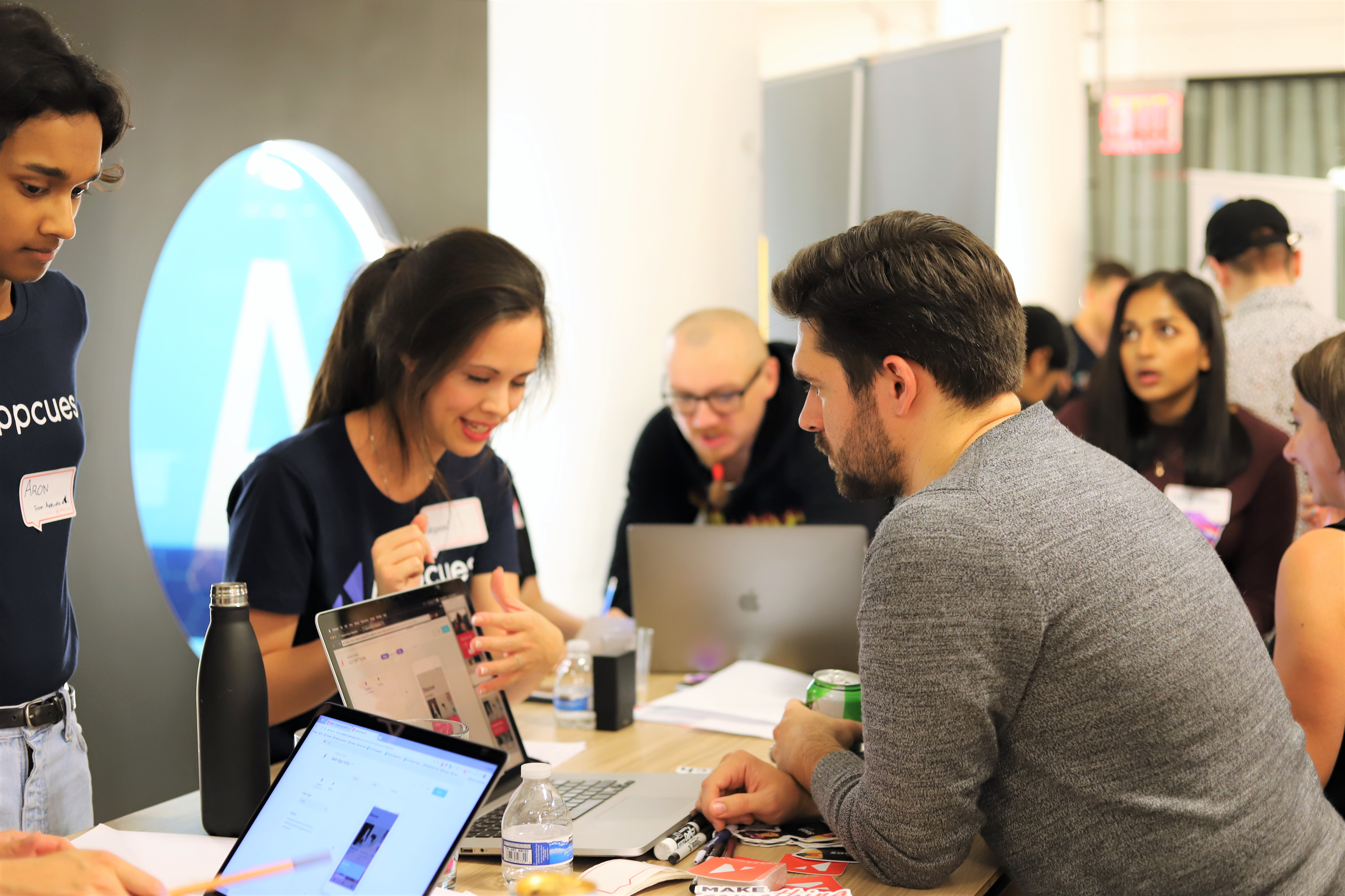 This is an image of people at  a user testing event hosted by Appcues called User Test Fest. Two engineers and developers are talking to a user tester and explaining features on a laptop.