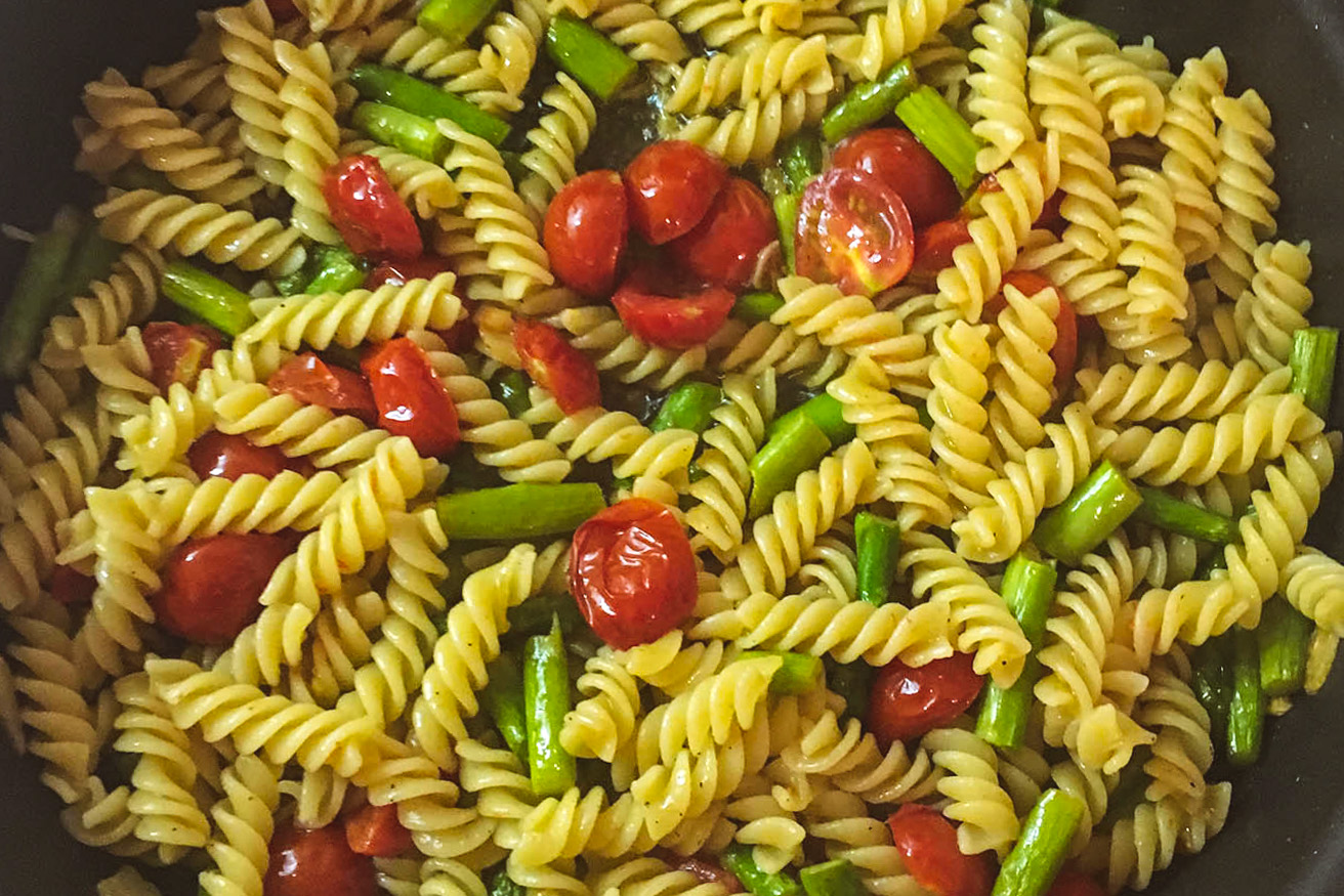 Summer asparagus, cherry tomato, garlic and oil pasta with basil and mint in a cast-iron pan