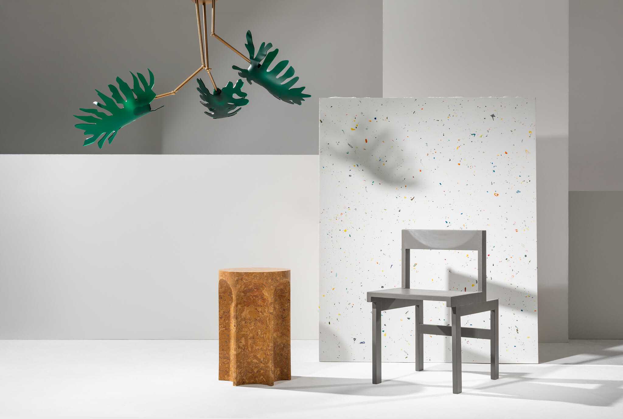 A chandelier with 'monstera leaves' (Urpflanze) hangs from the ceiling. A fluted marble-effect, mustard-coloured cylindrical side table (Chalk Plaster); a de stijl inspired dining chair (Mirrl); and a sheet of white surface material speckled with colourful inclusions (Mirrl) are all arranged in front of a minimalist backdrop of white boards.