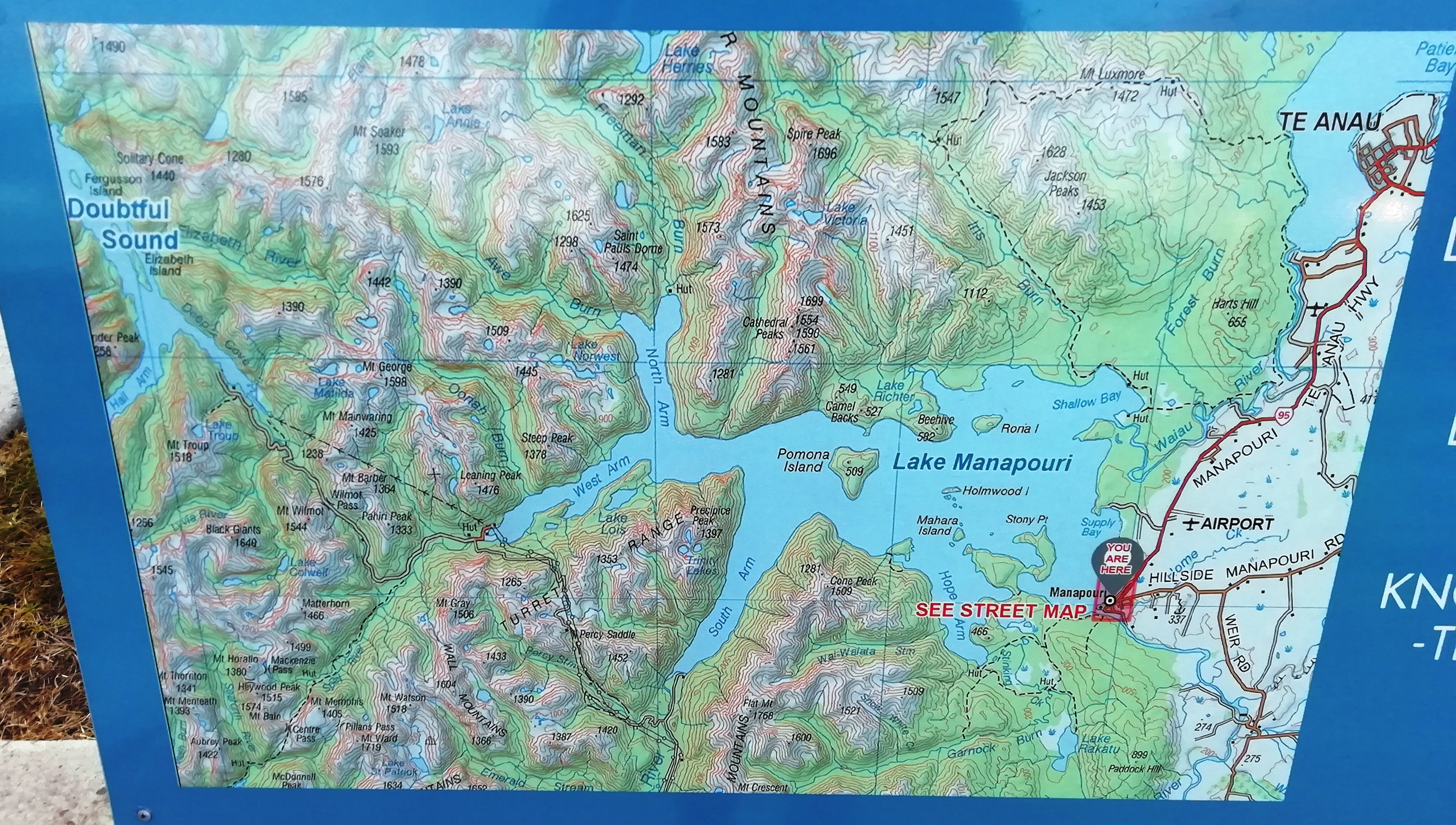 A topographical map of lake Manapōuri and environs on a signboard