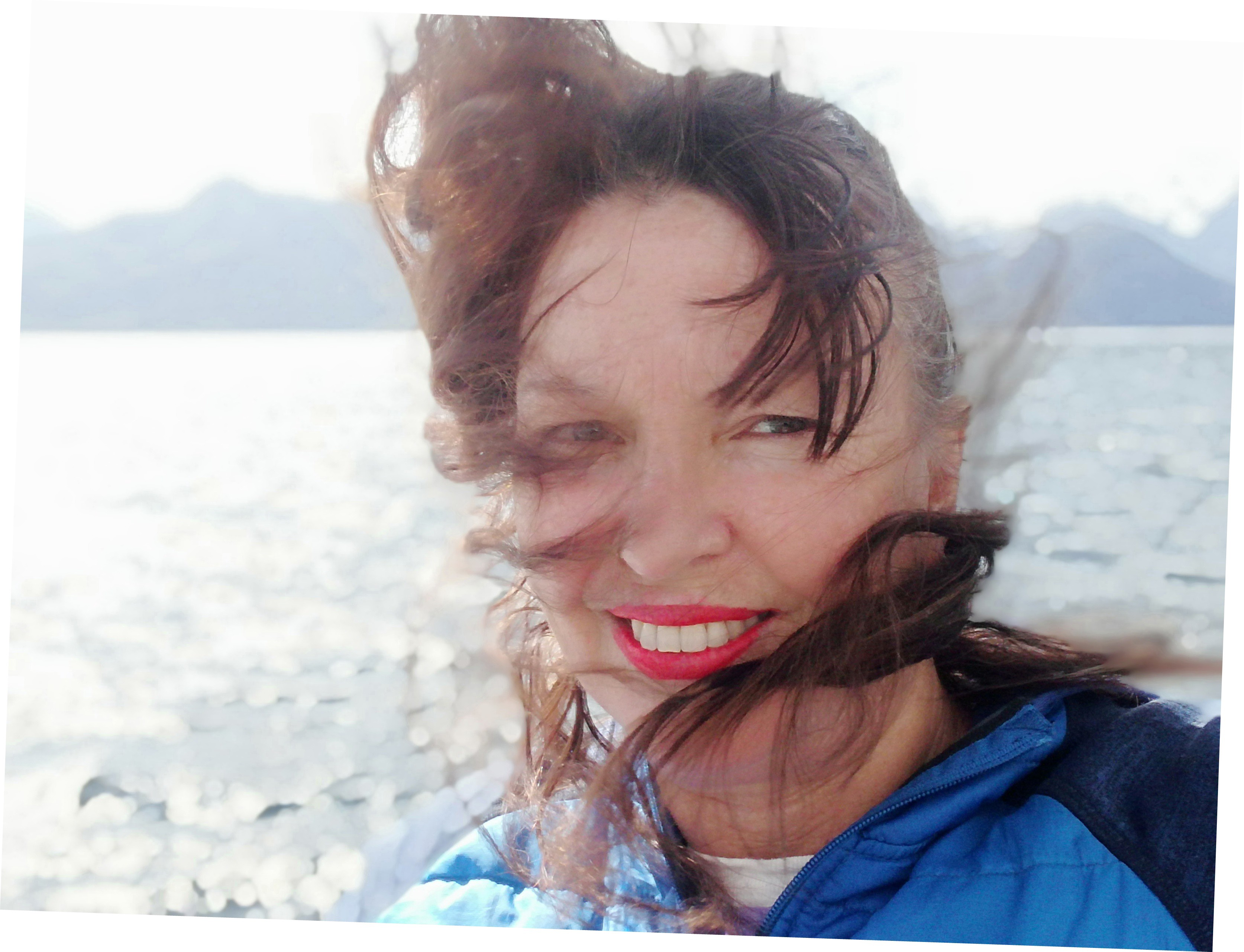 A photo of Mary Jane on a boat on Lake Manapōuri with hair being blown by the wind