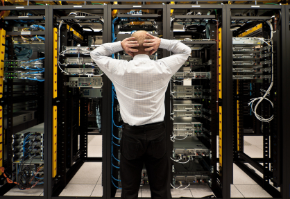 man standing with hands on head in front of computer room