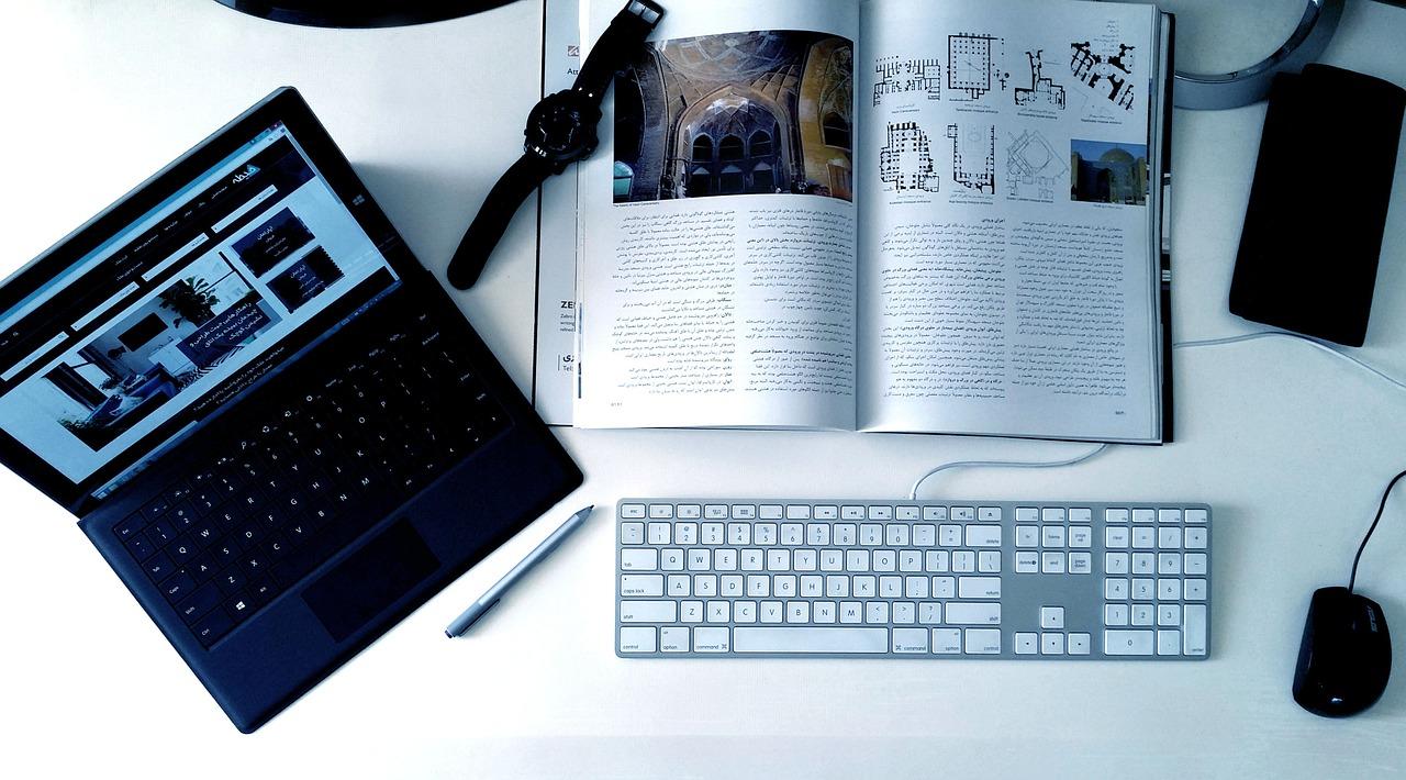 laptop computer, keyboard, open magazine, watch