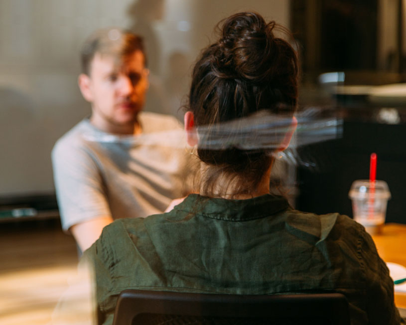 Back of woman's head talking to man