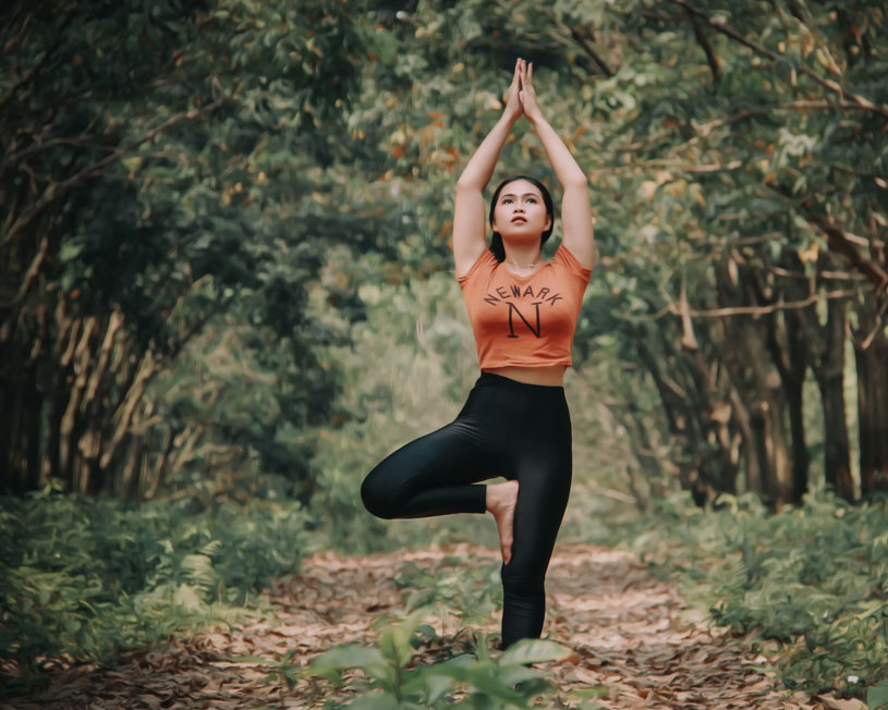 Woman in yoga pose in forest