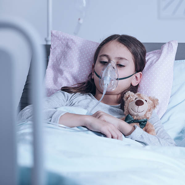 Girl with cystic fibrosis with a respirator holding a teddy in a hospital bed, illustrates need for complementary integrative medicine such as herbal remedies to supplement conventional treatment