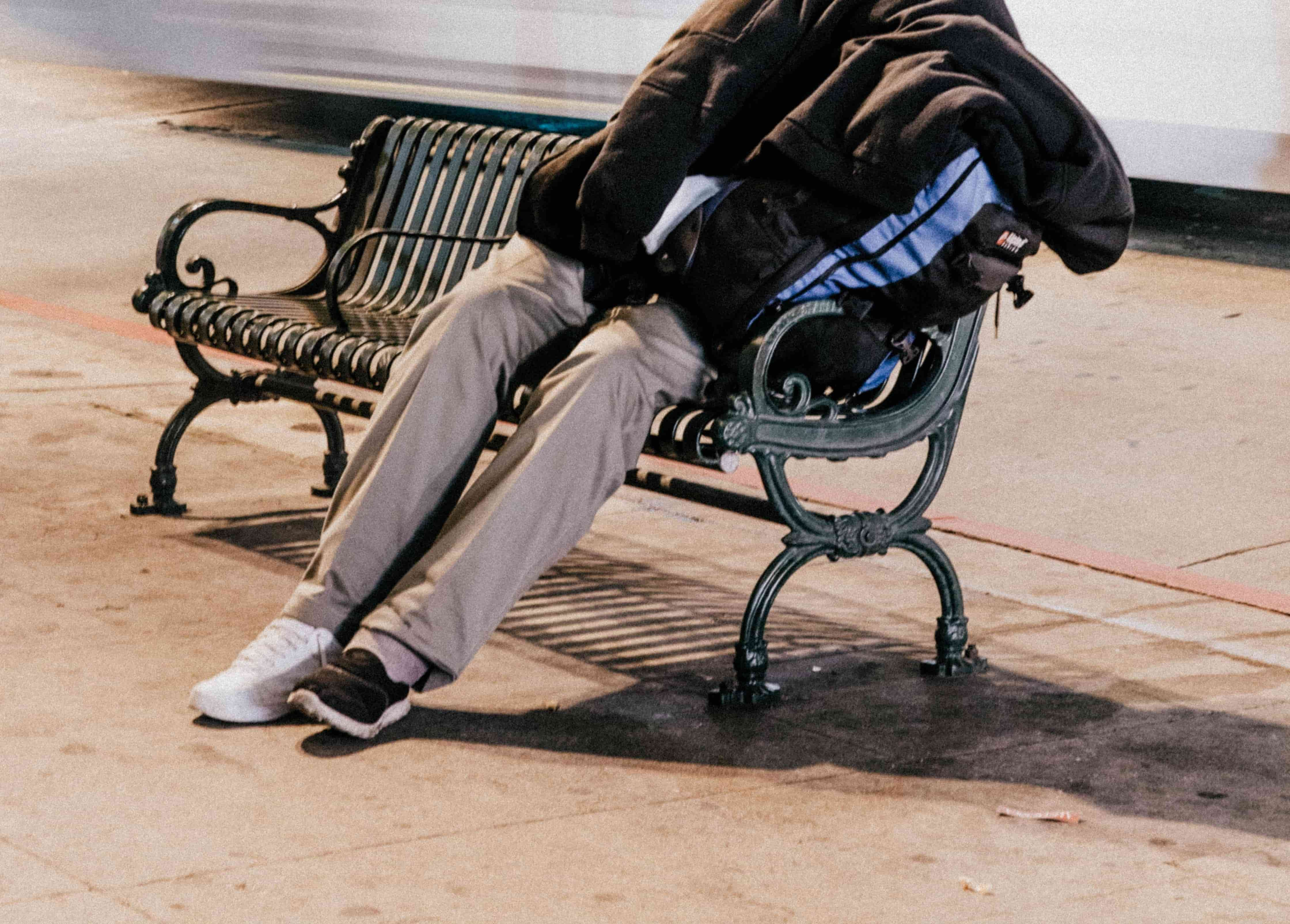 A photograph of a person sleeping on a public bench