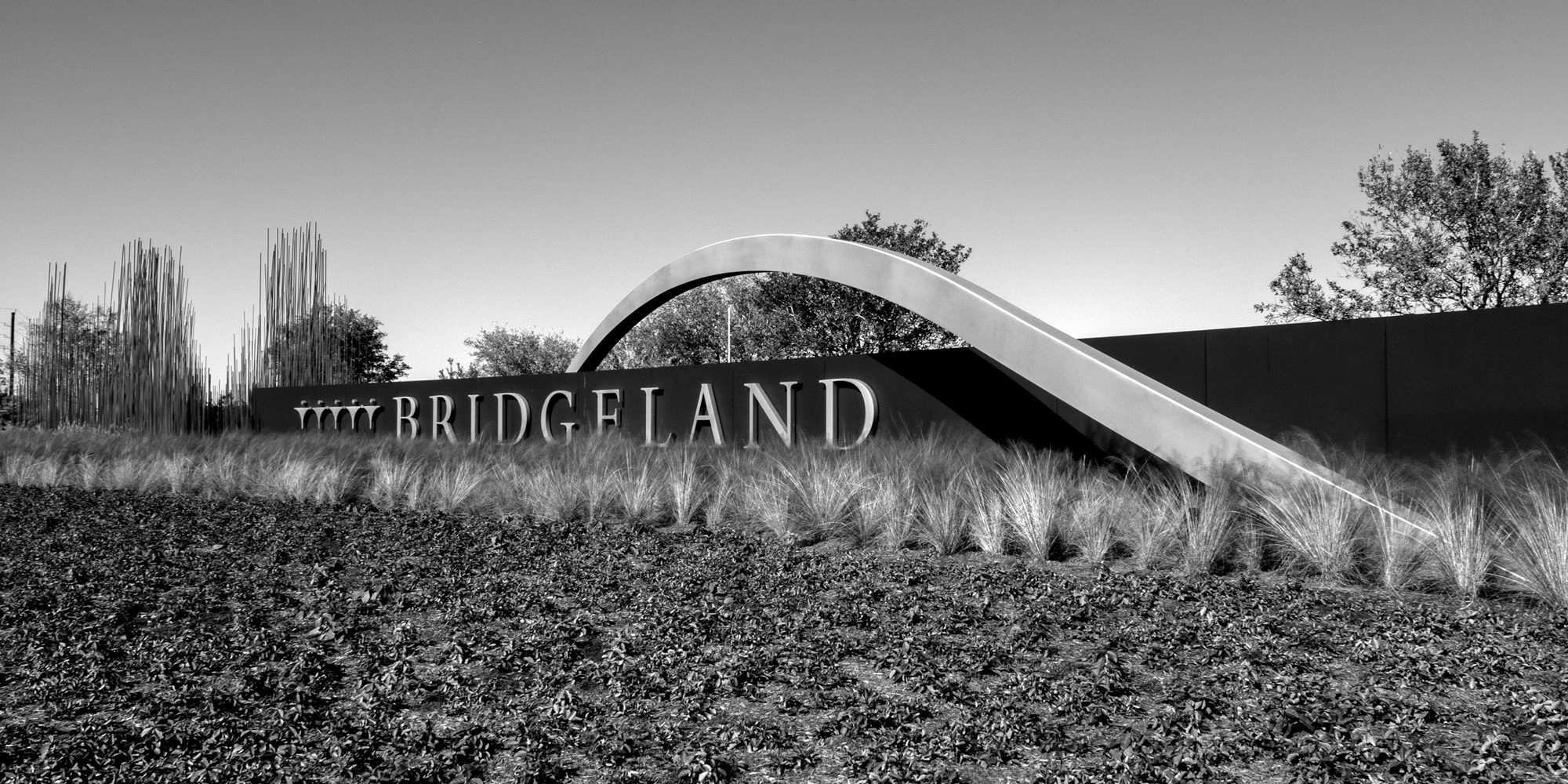 Bridgeland Community Gateway with large weathering steel monument wall with stainless steel arch and large channel letters