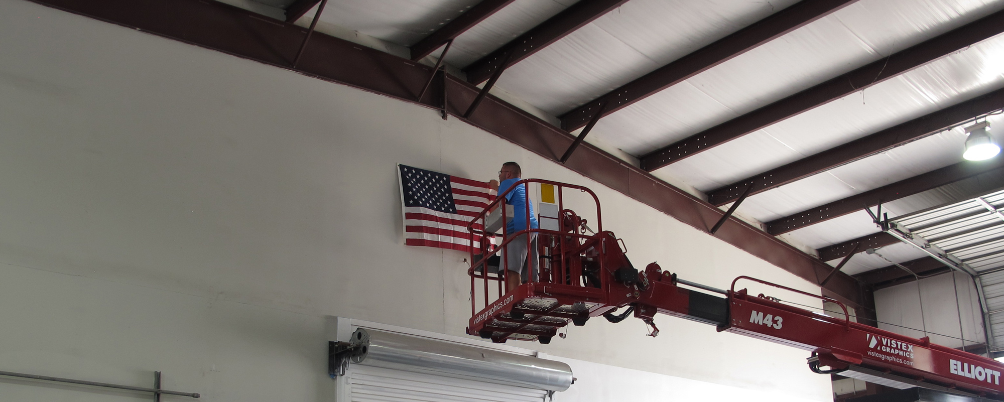 Owner using crane ruck to hang up the America Flag in manufacturing facility