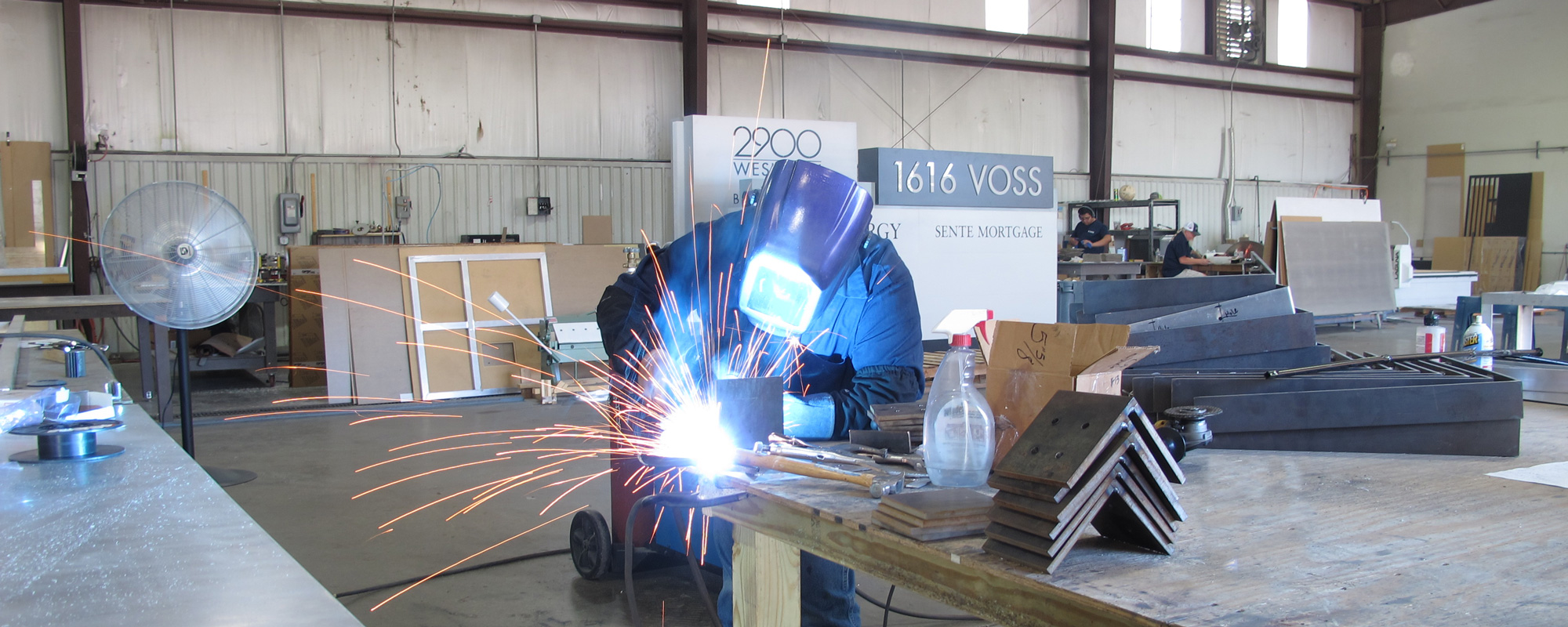 Fabricator welding at work table in manufacturing space