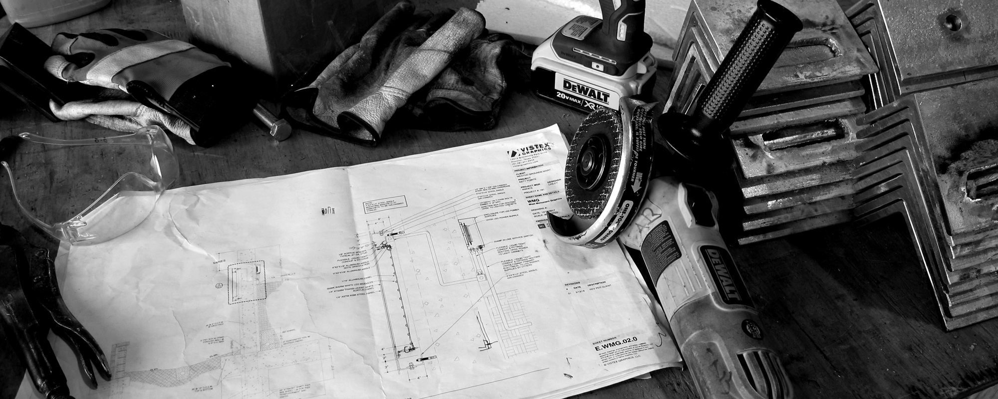 Hand tools, work gloves, and fabrication drawings on work table