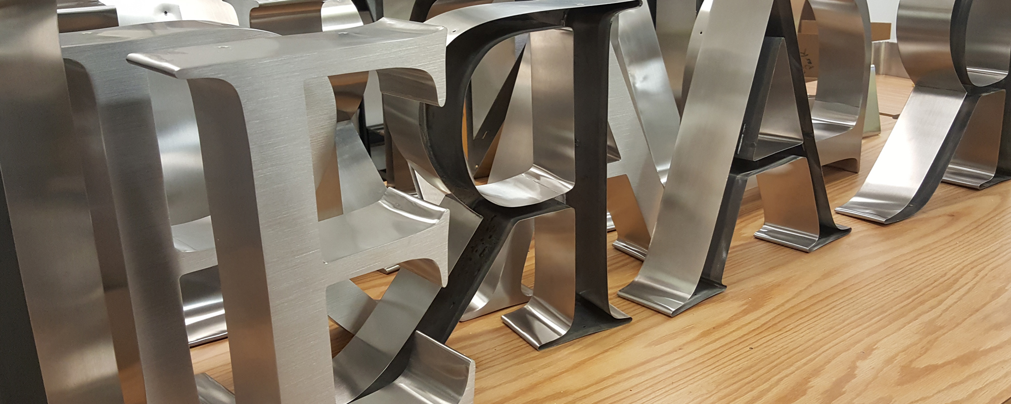 Stainless steel channel letters with brushed faces standing on table top