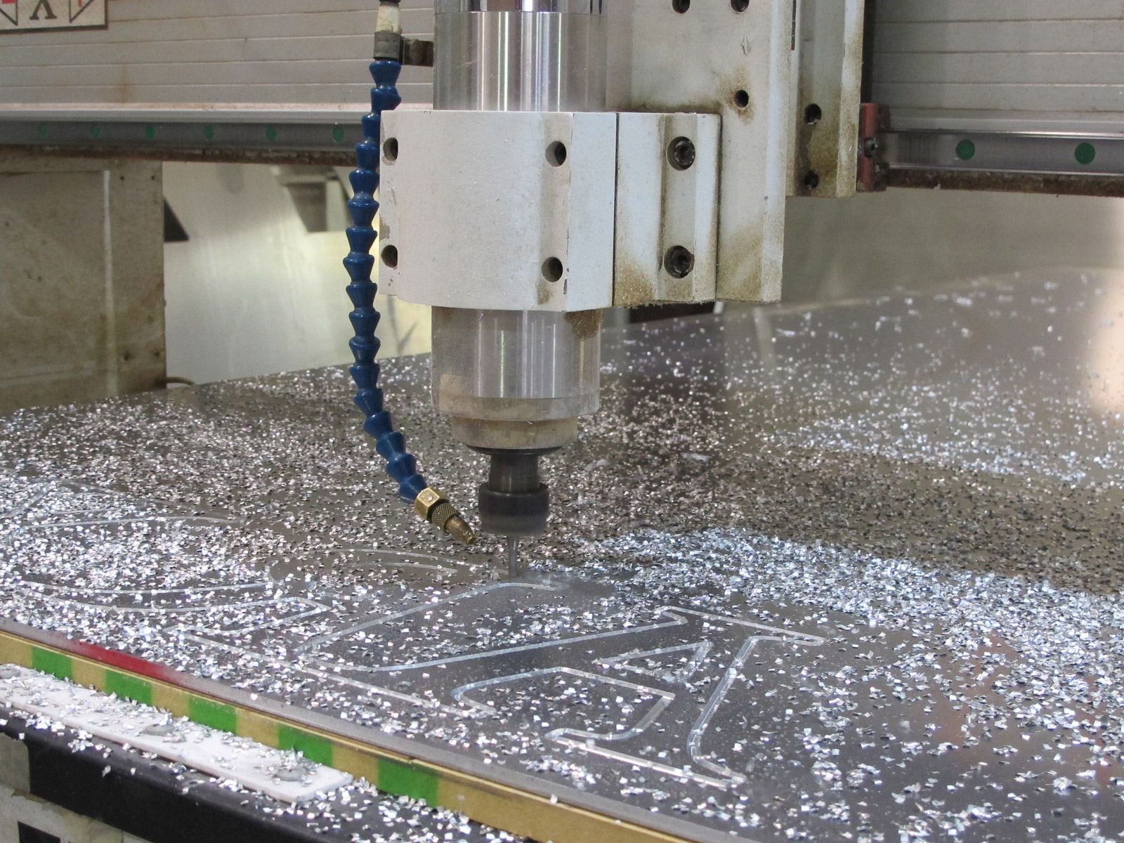 Large format CNC router cutting letters out of aluminum sheet