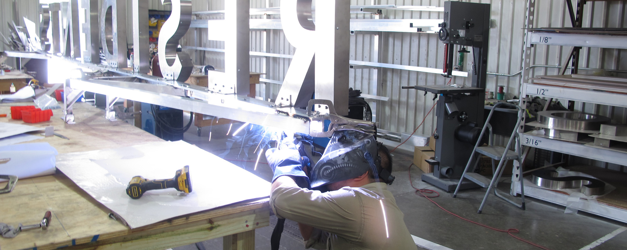 Fabricator welding aluminum structure to support dimensional letters