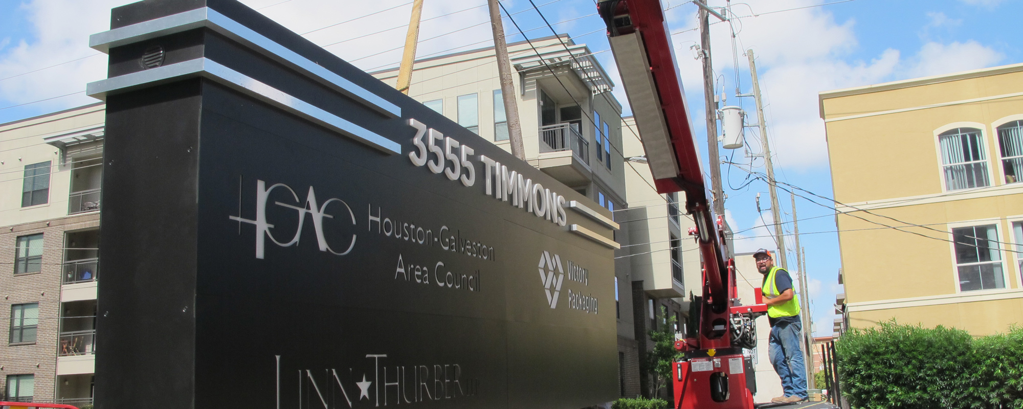 Installer using crane truck to install a monument sign
