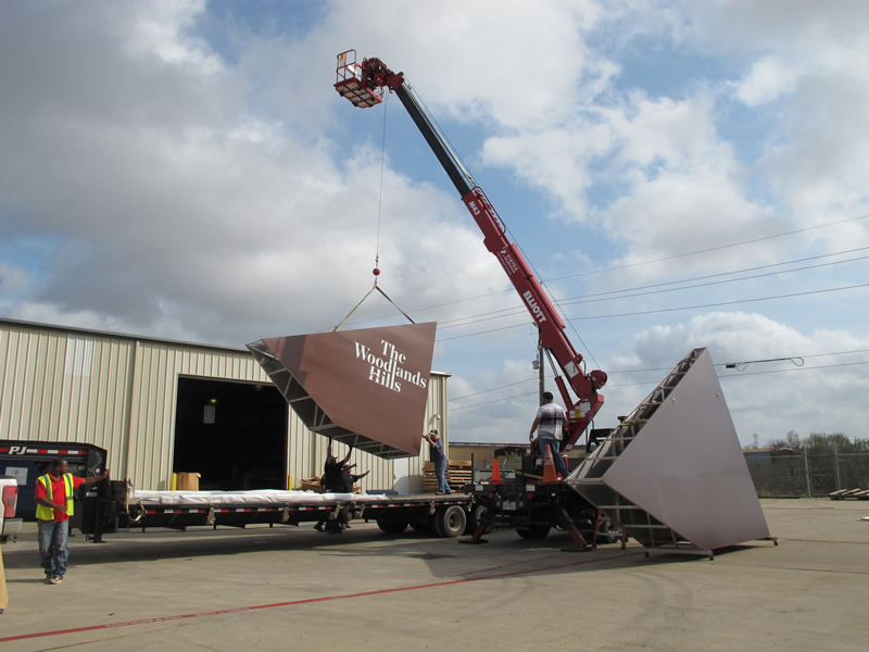 Install team using crane truck to load sign on trailer