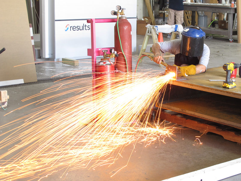 Fabricator using cutting torch on sign