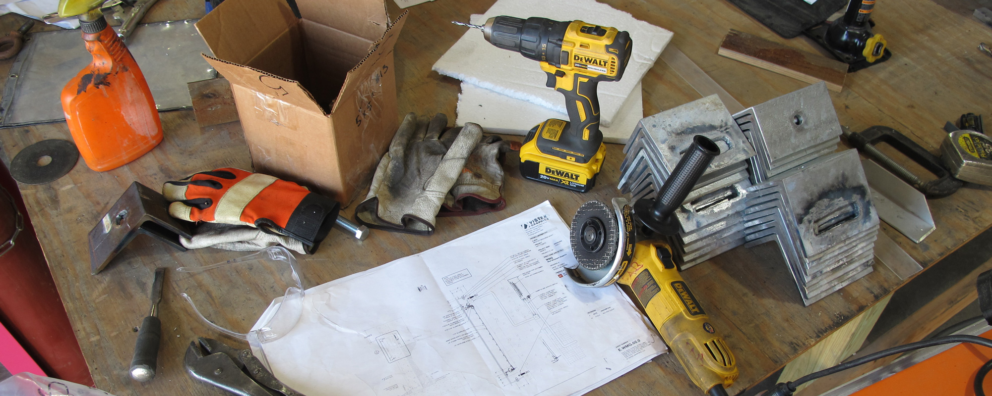 Various manufacturing tools, work gloves, safety glasses and fabrication drawings on work table