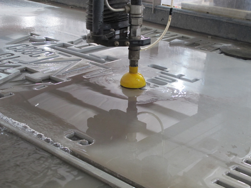 CNC waterjet cutting letters out of aluminum sheet