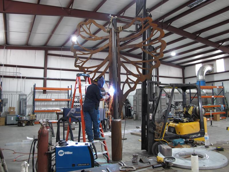 Fabricator welding large sculpture