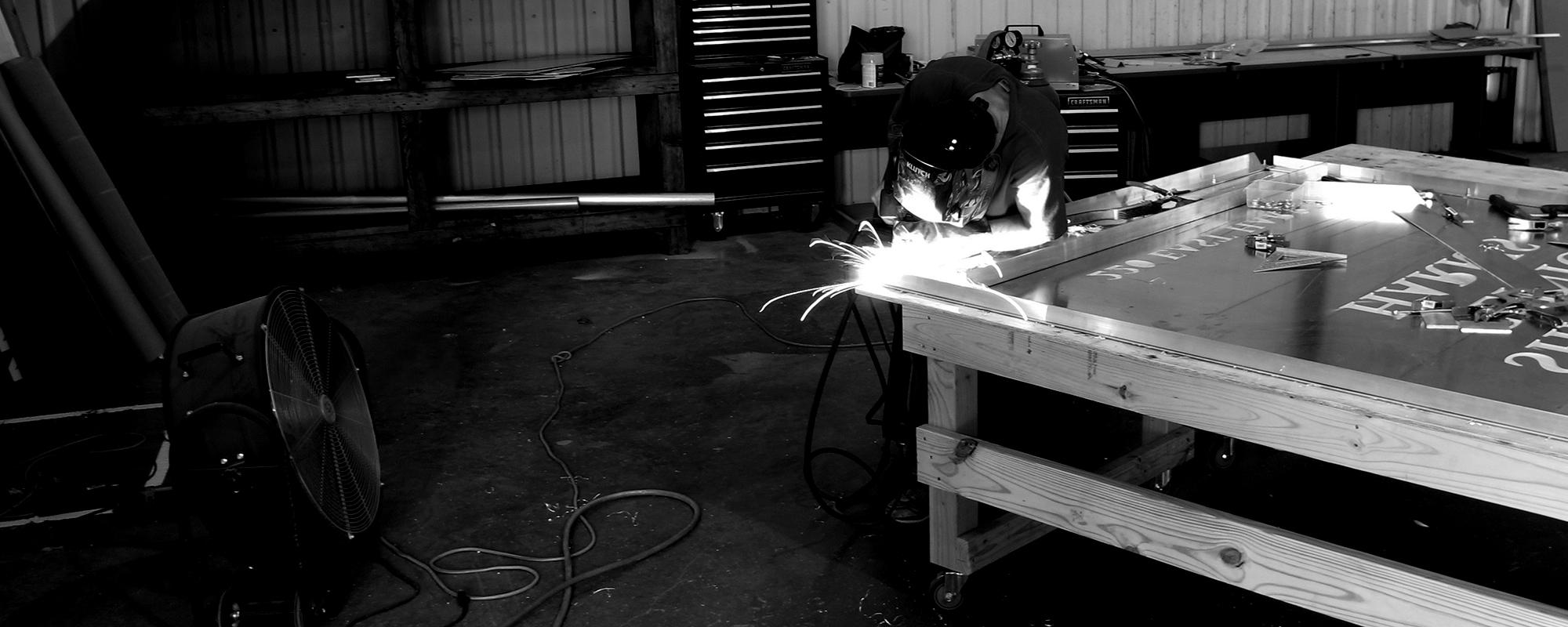 Fabricator welding sign cabinet