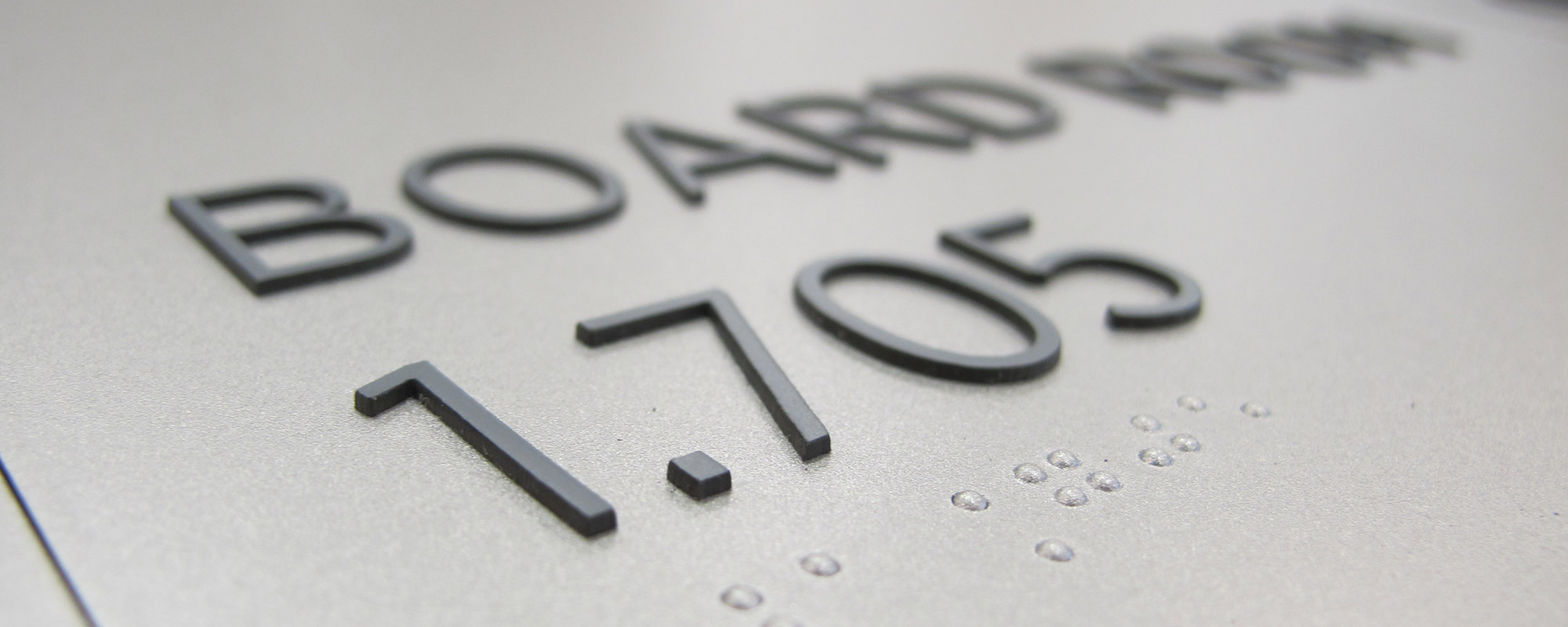 Closeup image of tactile copy and Braille on ADA sign