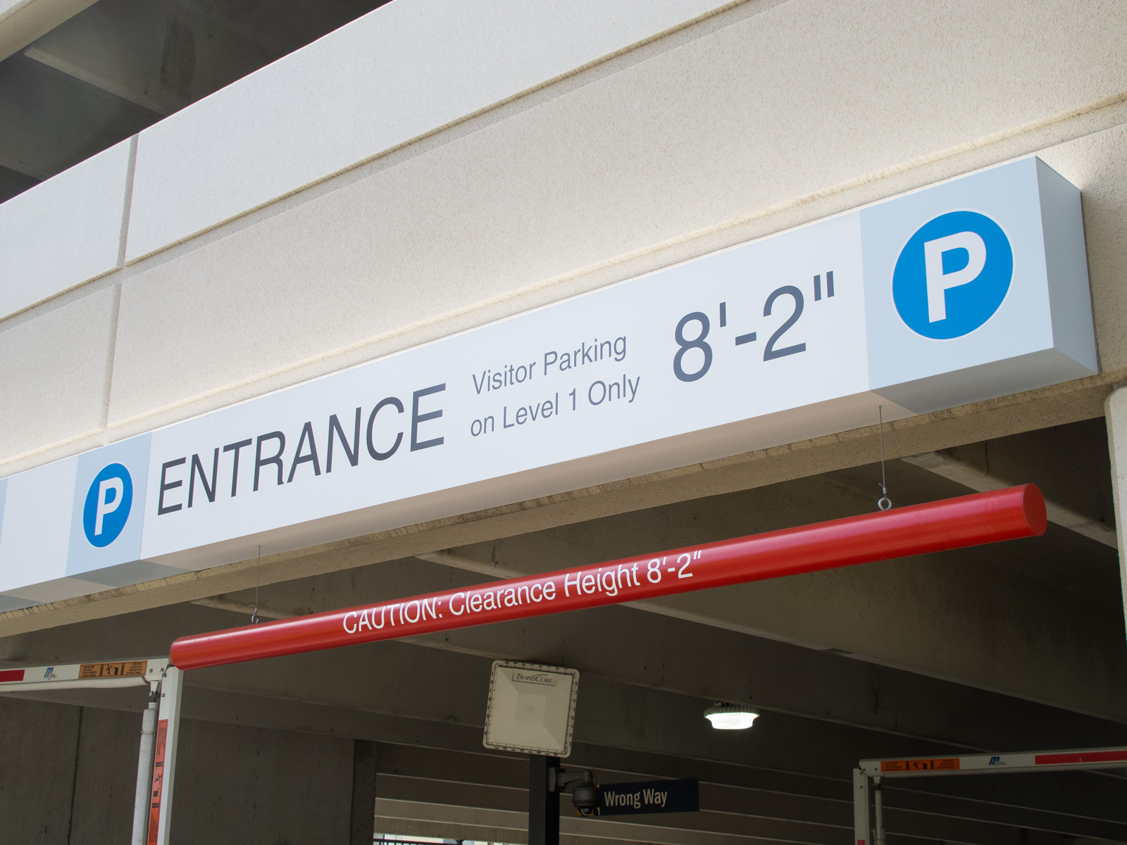 Close up view from side of fabricated entry and exit signage with clearance bar of parking garage.