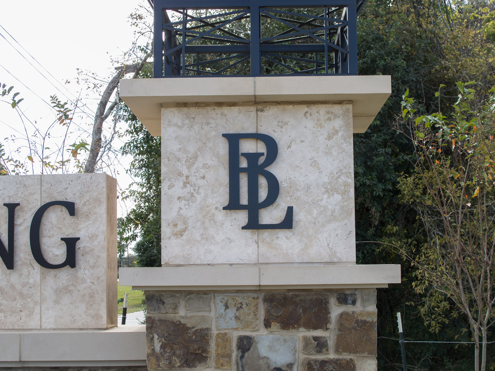 Close up view of dimensional aluminum logo mounted to monument tower.